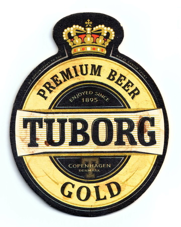 ST-PETERSBURG, RUSSIA - MARCH 3, 2019 - Vintage stained coaster (beer mat) with ad of Tuborg Gold beer.  Isolated on white background Redactioneel