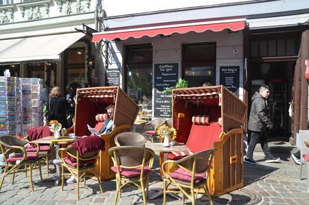 BERLIN, GERMANY - APRIL 9, 2019:  People have coffee on the open cafe terrace in Berlin, Germany