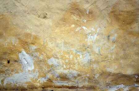 Yellow peeling paint on the old rough concrete surface — textured grunge background