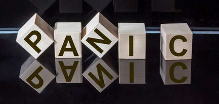 PANIC word made from wooden square letters on black glossy background. Mirror reflection. Stockfoto