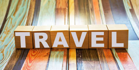 TRAVEL word concept written on wooden cubes blocks lying on a light table and light background
