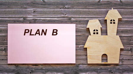 The text of plan B is written on a sticker, an icon of the house lies on a wooden table