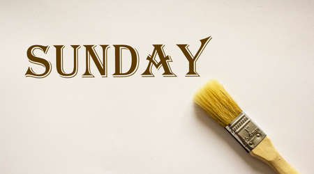 Sunday - written on a white sheet with a paint brush next to it 스톡 콘텐츠
