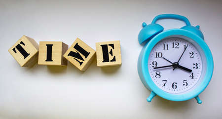 Close-up of an alarm clock near wooden blocks with the text time