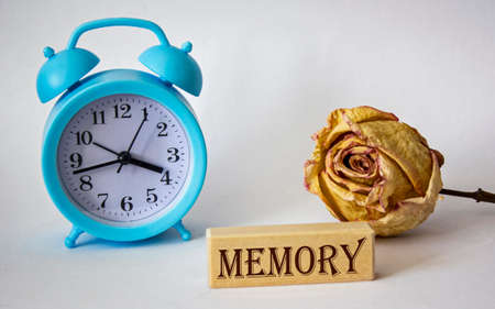 Text on wooden blocks. Memory. On a white background an alarm clock and a rose