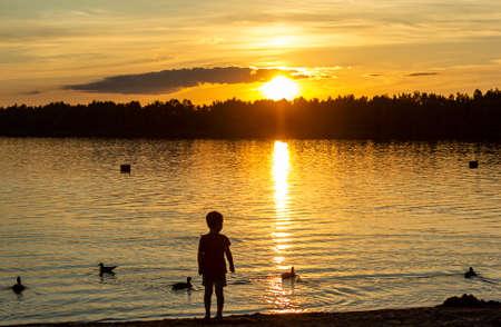sunset on the lake in the summer heat ashore silhouette child Standard-Bild