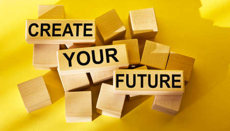 Create your future - lettering on wooden blocks on yellow background 스톡 콘텐츠