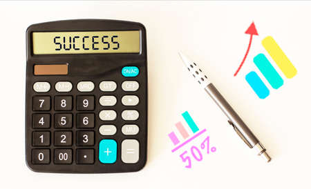 Text on a success calculator, pen and charts on a white background
