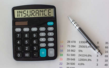 Tex insurance on a calculator with charts and pen on a white background