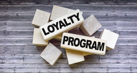 Loyalty program text on wooden blocks and on brown table