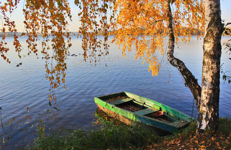 Lonely boat at the pier on the lake in autumn. Stock Photo