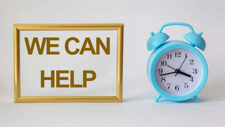We can help, text in a gold frame on a white background, near a blue alarm clock Imagens