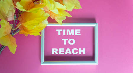 time to reach, text in silver frame on yellow foliage and red background