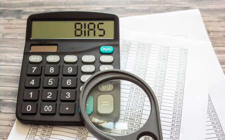 Bias, text on a calculator with documents and a magnifying glass on them. Business, finance conceptual.