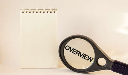 Overview, the text is written on a magnifying glass next to a notepad. White background