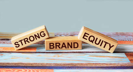 Wooden blocks with the text STRONG CAPITAL BRAND on a colored wooden background. Place to write