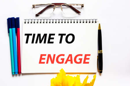 Time to engage, the text is written on a notebook, next to glasses, a pen and felt-tip pens on a white background.