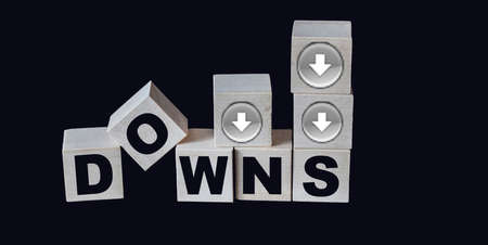 Down text and down arrows are written on wooden blocks and black glass background 免版税图像