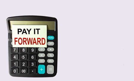 The phrase Pay It Forward on a sticker posted on a calculator and a white background.