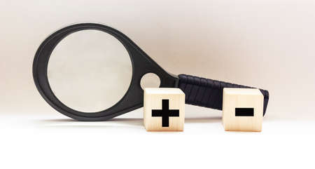Two wooden cubes with mathematical symbols plus and minus, near a magnifying glass on a white background Stockfoto