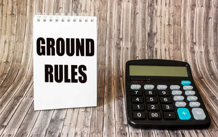 the text GROUND RULES is written on a notebook, next to it lies a caddy calculator on a wooden