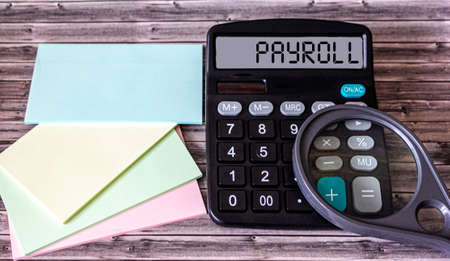 Payroll words on calculator display and on wooden background, financial concept