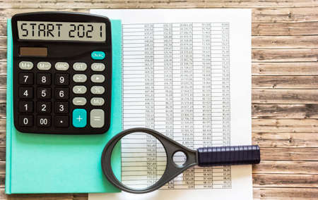 The start 2021 is written on the display of the calculator, on the desktop with financial documents and a magnifying glass. Business concept.