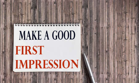 Make a good first impression written on notepad and wooden table