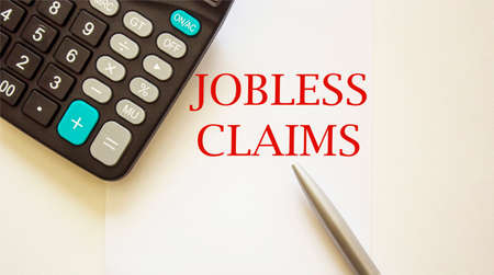 Jobless Claims, form on white background with calculator and pen and white background. Banque d'images