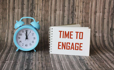 Text, the word Time To Engage is written in a notebook lying on a wooden table with an alarm clock. Business concept