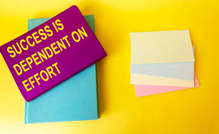 The text Success Depends on Effort is written on a colored notebook that lies on a yellow background Imagens