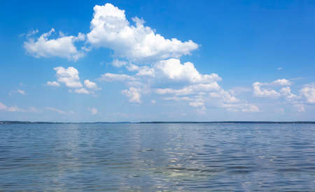 Summer heat on the lake with blue sky and white clouds Standard-Bild