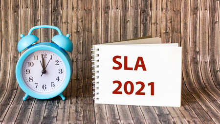 Service Level Agreement SLA 2021 - word on notepad and wooden background. Business and finance concept