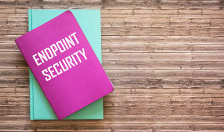 Handwritten text Endpoint Security on notepad. Concept means corporate network protection methodology wooden office background.