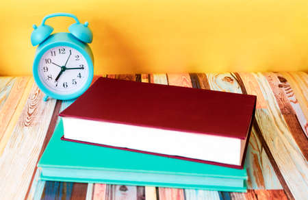 Alarm clock and two notepads on the desktop.