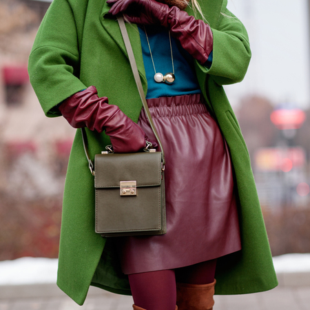 Street and bright style. Young girl in a green coat, stylish leather skirt. Details. Sguare image photo 免版税图像