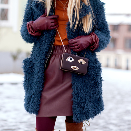 Street and bright style. A young girl in a fur coat, a stylish leather skirt. A fun bag. Details. Sguare image photo Archivio Fotografico