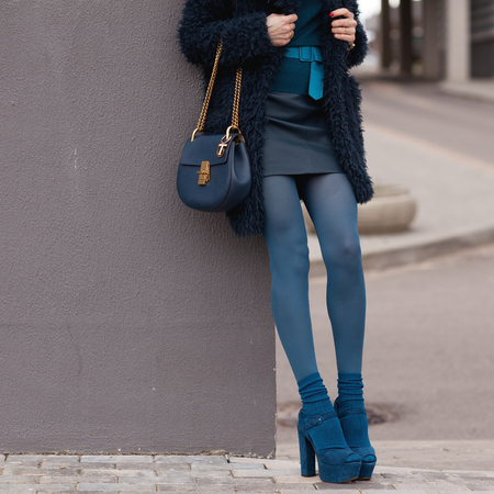 Street, bright style. A young girl in a blue fur coat with a handbag in heels. Details. Sguare image photo