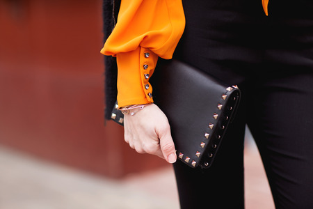 Street, office, bright style. Young woman, business style, black jacket, black pants, black handbag, sunglasses, orange blouse, belt, bracelet. Details.