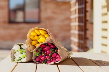 Beautiful colorful bouquets of tulips in craft paper lie on the street on a wooden table. Side view Imagens