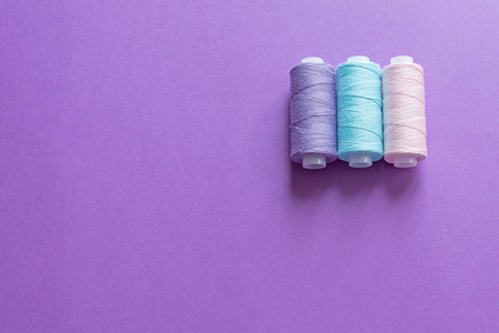 A set of sewing thread on a colored background, top view Stockfoto