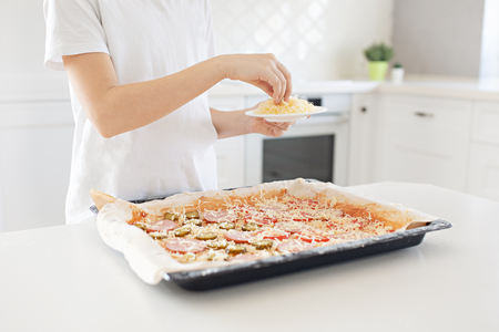 Cooking concept - cook manually adding grated cheese to pizza in the home kitchen. Close-up