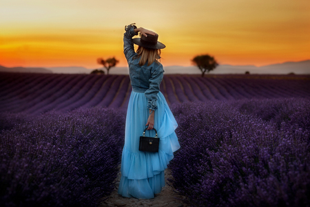 Stylish girl in a gently blue dress and a black hat stands in a lavender field and looks at a beautiful sunset. Imagens