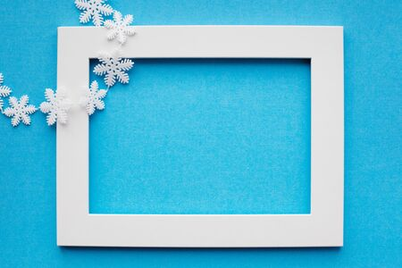 White frame and snowflakes on a blue background. New year, holiday, decoration. With place for text. View from above