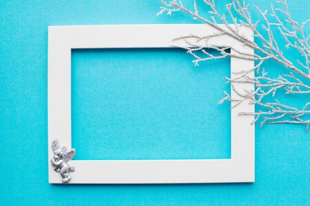 White frame, silver branch and an angel on a blue background. New year, holiday, decoration. With place for text. View from above Фото со стока