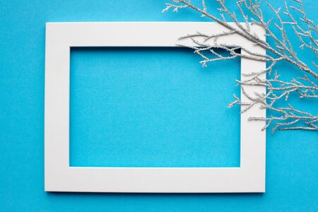 White frame, silver branch on a blue background. New year, holiday, decoration. With place for text. View from above