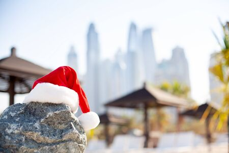 Santa hats on the beach overlooking the sea and the beautiful city of Dubai. Christmas and New Year holidays in the concept of warm countries.