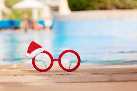 Red Christmas glasses with Santa hat near the pool. Christmas holiday concept. Фото со стока