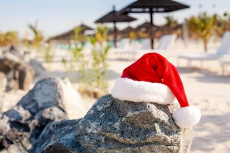 Santa hats on the beach. Christmas and New Year holidays in the concept of warm countries.