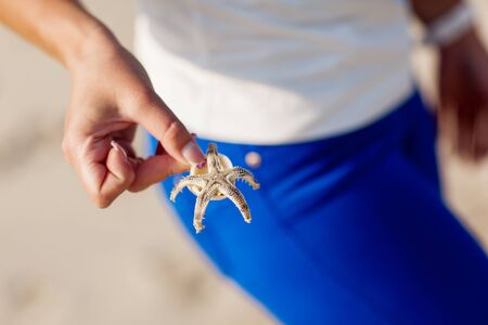 Girl's hand holds a starfish on a blue background Stock Photo
